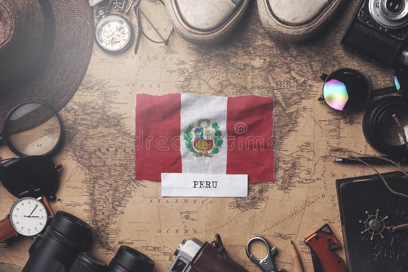 Peru Flag Between Traveler`s Accessories on Old Vintage Map. Overhead Shot.  royalty free stock photos