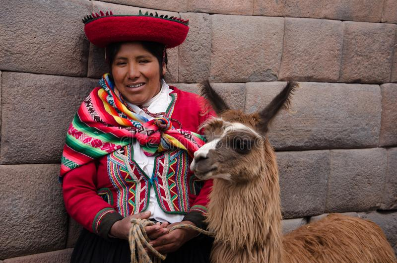 Peru lady in local costume poses with her llama. Peru near Cusco, native lady walks with her llama. She is wearing traditional costume and poses for the stock image
