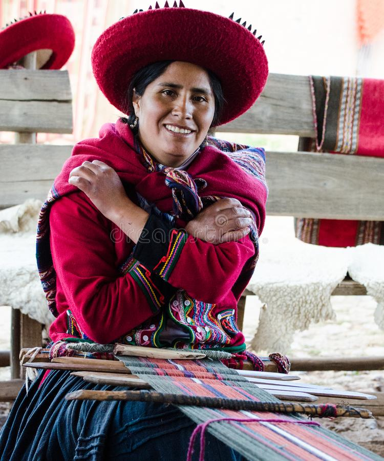 Peru, lady weaver, poses at her loom while weaving native garments. Peru, Peruvian lady, looks up from loom where she is weaving native Peruvian garments royalty free stock images