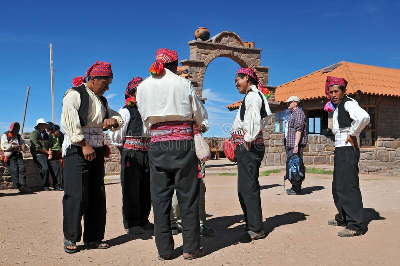 Men dressed in traditional outfits specific for the Taquile Island having a conversation in main square, Lake Titicaca, Peru.  royalty free stock image