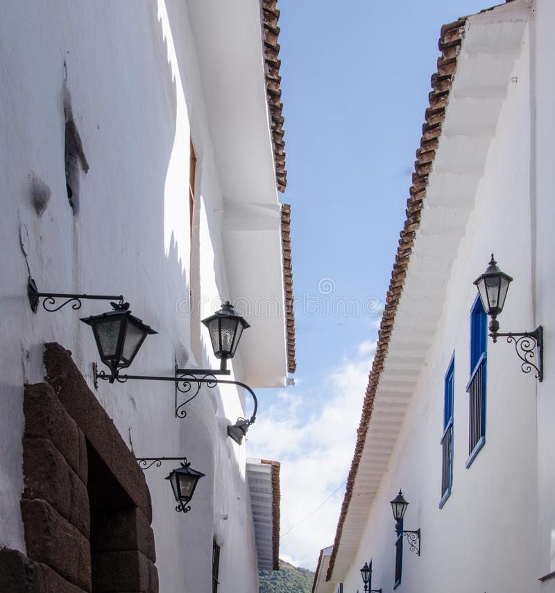 Peru, May, Cusco white walls, blue rectangular framed windows, walls converge to narrow opening to blue sky stock photo