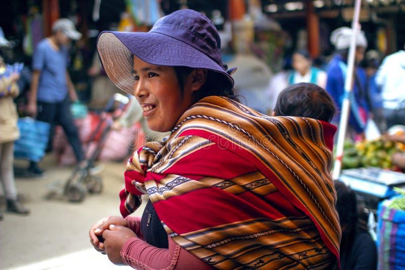 Peruanische einheimische Mutter bringt ihren Babysohn auf ihr zur?ck stockbilder