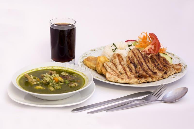 Peruanischer Teller: Hühnersuppe des Korianders, des morada Aguadito de Pollo) +chicha (purpurroter Maissaft) und des Huhns gegri lizenzfreies stockbild