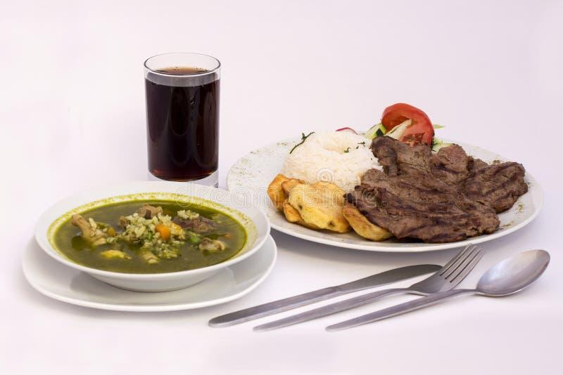 Peruanischer Teller: Hühnersuppe von Koriander (Aguadito de Pollo) +chicha morada, Rindfleisch grillte mit Reis stockbild