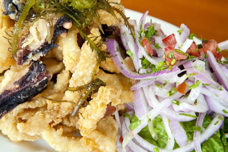 Peruanisches Lebensmittel: gebratene Fische (chicharron) kombiniert mit Meeresfrüchten lizenzfreie stockfotos
