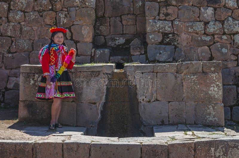 Peruansk infödd kvinna vid en springbrunn, Cusco arkivfoton