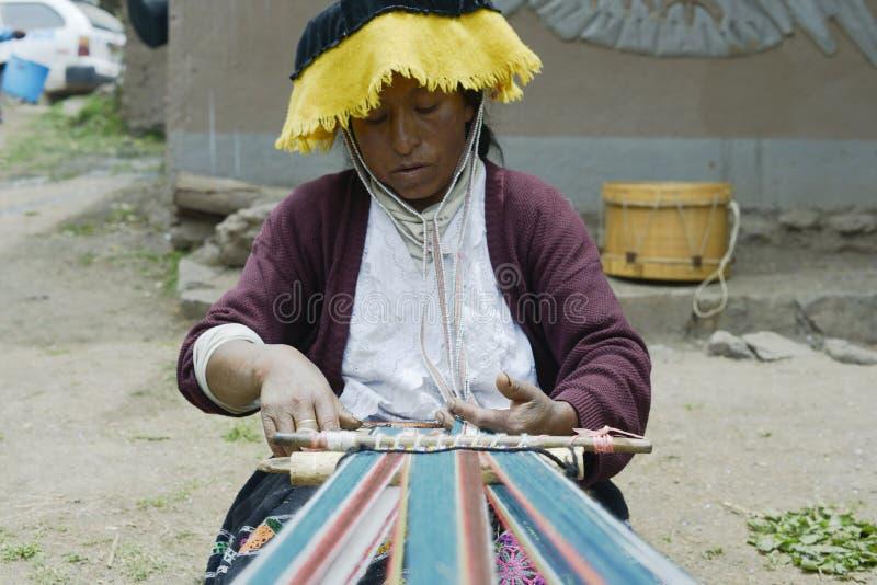 Peruansk kvinna som väver torkduken på en handvävstol arkivbilder