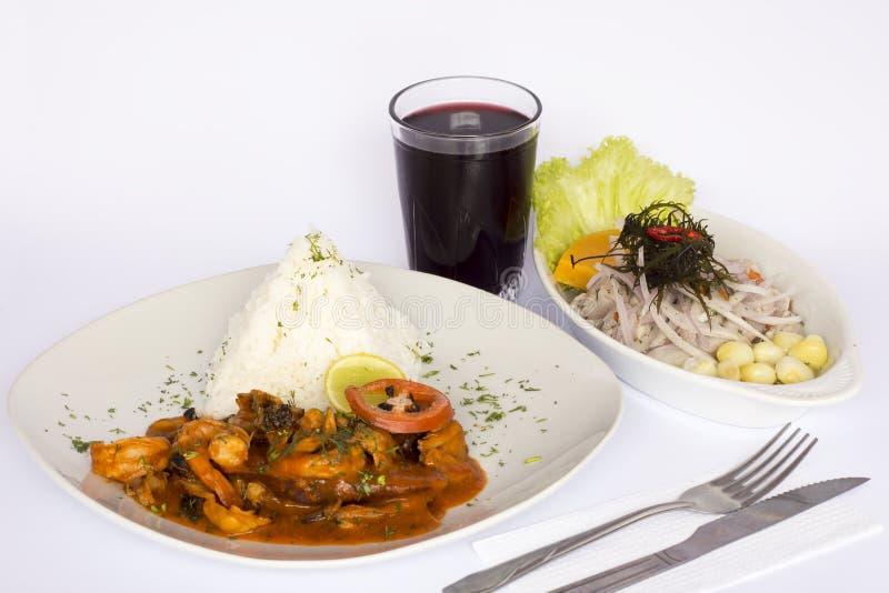 PERUANSK MAT: Äta lunch Cebiche och Picante de Mariscos med ris och ett exponeringsglas av chichamorada arkivbild