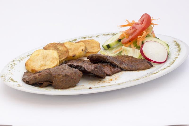 Peruansk maträtt: anticuchos, grillat skewered nötkötthjärtakött med den kokta potatisen och sallad arkivbild