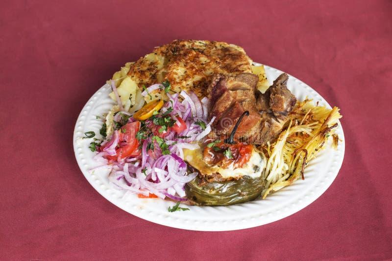Peruansk maträtt: Doble från Arequipa Stekt svin (Chicharron), slog potatisar (pastell de far), lök, tomater, spagetti med c royaltyfria foton