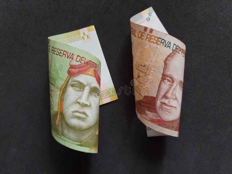 peruanska sedlar av olika valörer och svart bakgrund arkivfoto