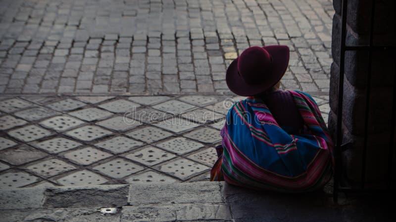 Peruanskt kvinnasammanträde på gatan av Cuzco, Peru royaltyfri foto