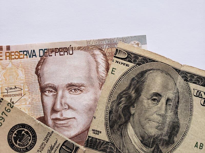 Peruviaans bankbiljet van twintig zolen en gebroken Amerikaans bankbiljet van 100 dollars