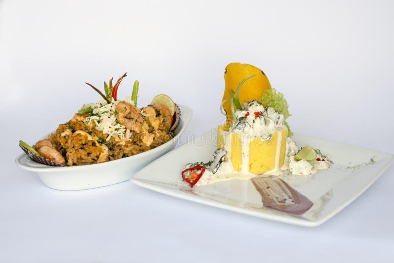 Peruviaans Voedsel: Causa Rellena, A brak popatoes gevuld met krabmaaltijd en Rijst met overzees voedsel 2 die schotels als hoofd stock afbeeldingen