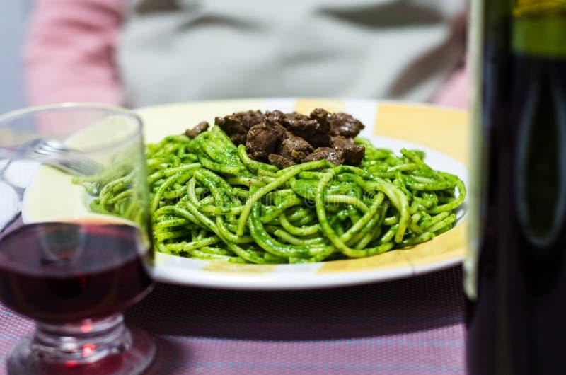 Peruviaanse spaghetti met vlees en room van groen die basilicum van hierboven op een witte plaat wordt bekeken stock foto's
