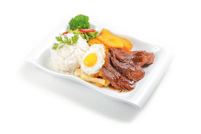 Peruviaanse voedsel of lomosaltado met gebraden ei stock afbeelding