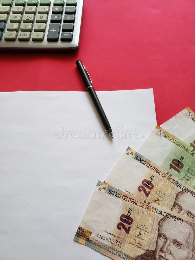 peruvian banknotes,  black pen, white sheet of paper and calculator on the red table royalty free stock image