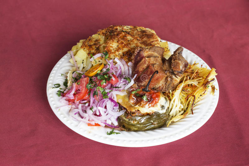 Peruvian Dish: Doble from Arequipa. Fried pig (Chicharron), smashed potatoes (pastel de papa), onion, tomatoes, spaghetti with c royalty free stock photos