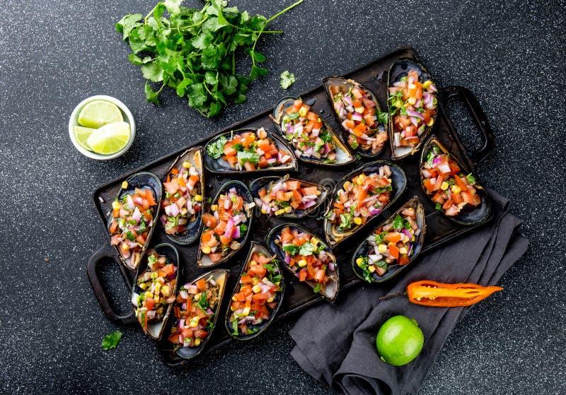 PERUVIAN FOOD. Choros a la chalaca. Big mussels, choros zapatos seasoned with purple onion, tomatoes, corn and lemon stock photography