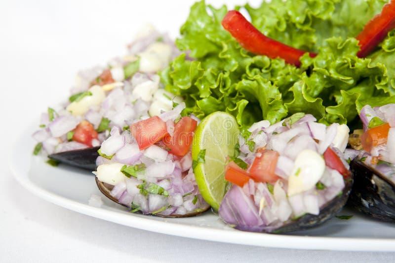 Peruvian food: Choros a la chalaca, mussels seasoned with onion, tomato and lemon royalty free stock photos