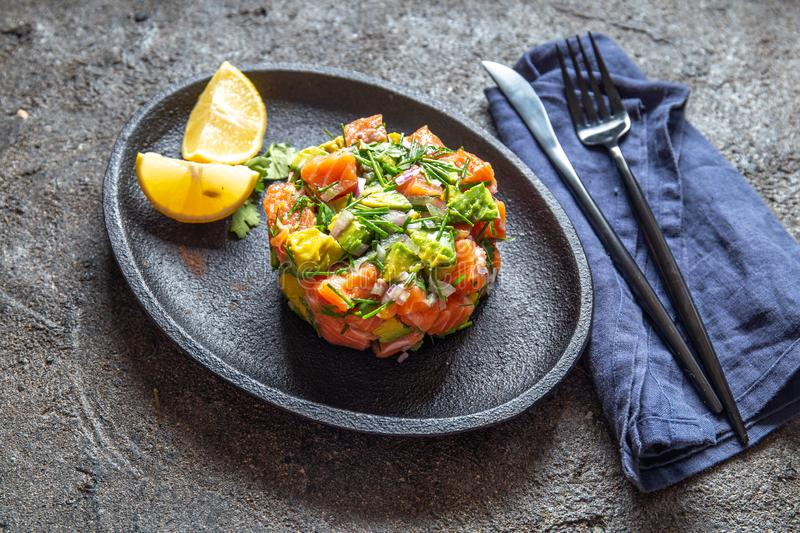 PERUVIAN NIKKEI FOOD. Salmon avocado ceviche on black plate, black background top view royalty free stock photo
