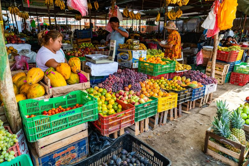 Peruvian people buy and sell fruits in the market at Nazca Peru stock photo