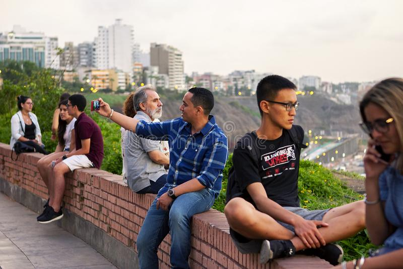 Peruvian people and tourists watching the sunset and taking selfies royalty free stock photos