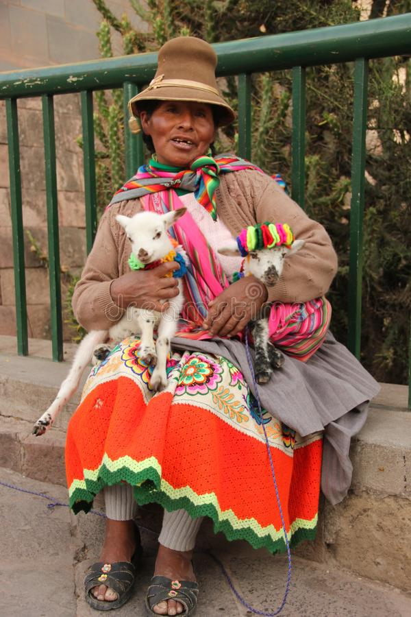 A Peruvian woman and her goats. A Peruvian woman in traditional clothing is posing with her baby goats in the historical centre of Cuzco, Peru stock photos