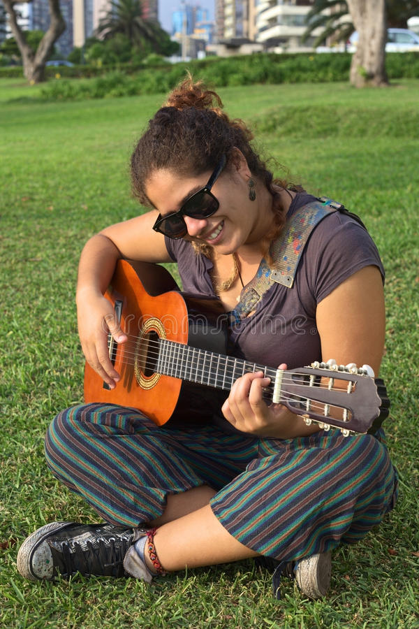 Peruvian Woman Playing the Guitar. Beautiful smiling young Peruvian woman playing the guitar in a park (Selective Focus, Focus on the face of the woman royalty free stock image