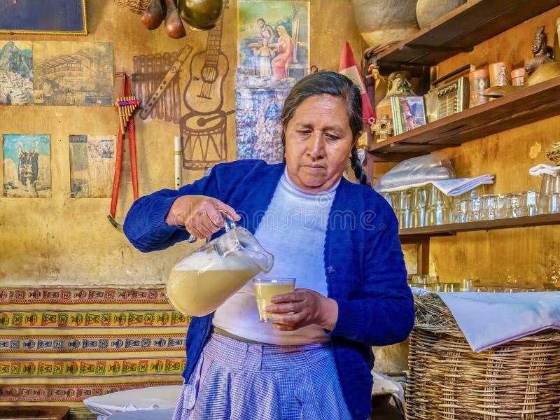 A Peruvian woman serving chicha in Peru. royalty free stock photos