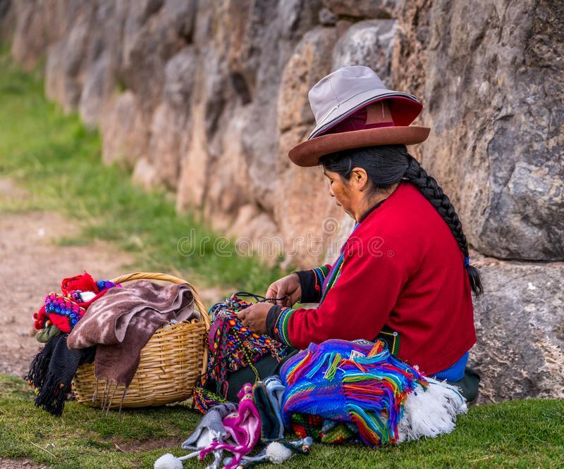 Peruvian woman sewing and making clothing while selling at tourist destination royalty free stock image