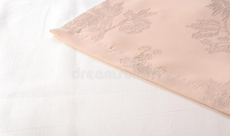 Perzik-gekleurd servetclose-up op witte tafelkleedachtergrond stock foto's