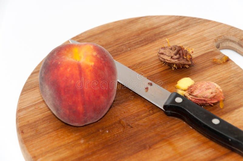 Perzik met perzikkuilen en mes op de scherpe raad stock foto