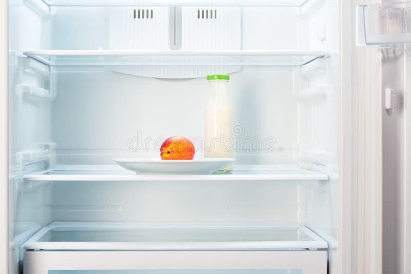 Perzik op witte plaat met fles yoghurt in ijskast stock foto's