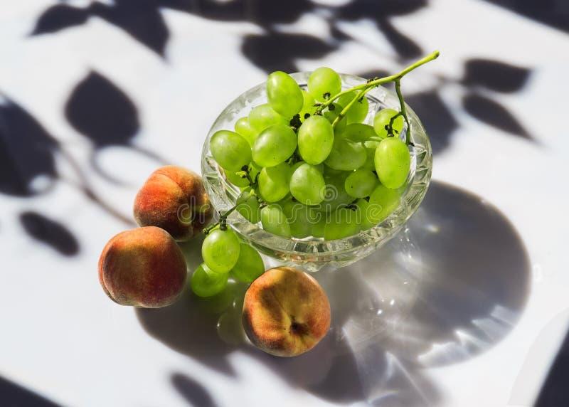 Perziken en druiven in een kom van de kristalsalade stock foto's