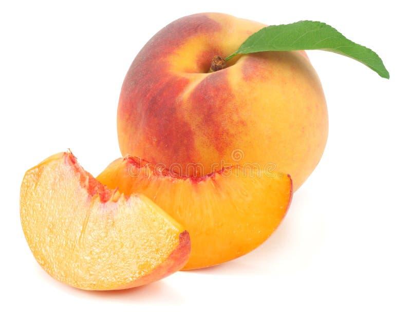 perzikfruit met groen die blad en plakken op witte achtergrond worden geïsoleerd royalty-vrije stock afbeelding