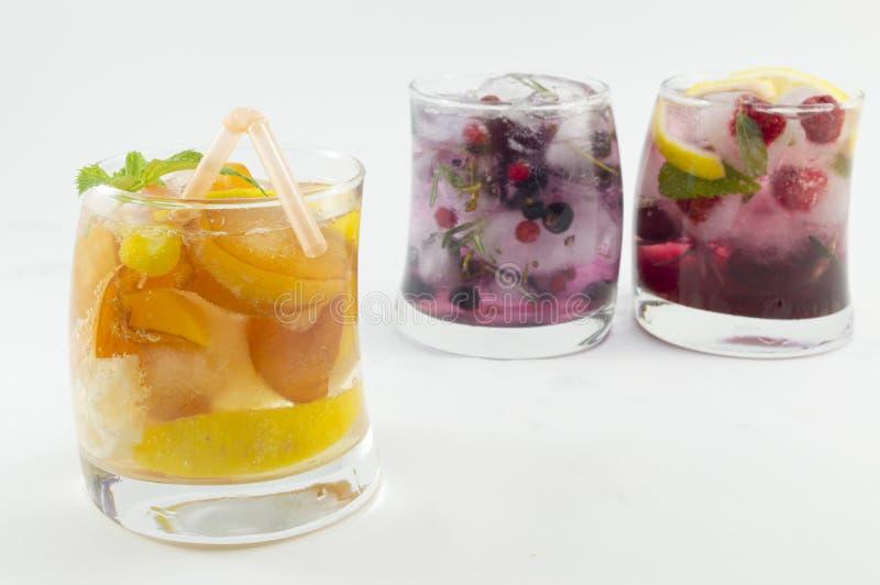 Perziksap met perzikplakken in een bochtig glas op groene backgr stock afbeelding