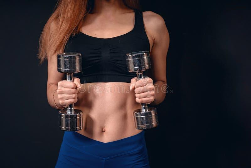 Pesa de gimnasia atlética de las elevaciones de la muchacha ejercicio para el bíceps con pesas de gimnasia imagen de archivo