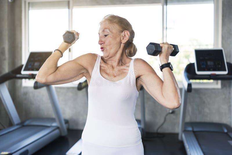 Pesa de gimnasia de elevación del ejercicio mayor de la mujer en gimnasio de la aptitud foto de archivo libre de regalías