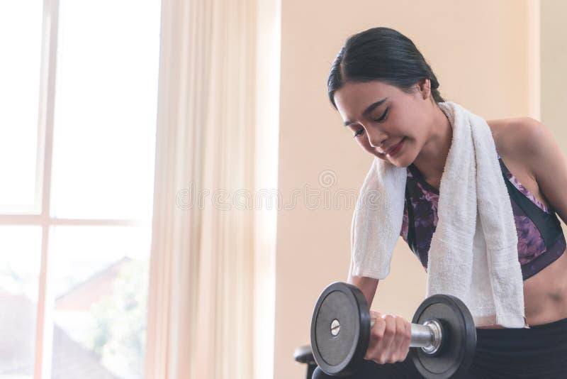 Pesa de gimnasia de elevación de la mujer flaca asiática fuerte en aptitud fotografía de archivo libre de regalías