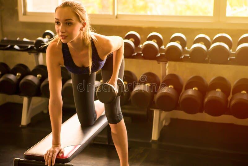 pesa de gimnasia de elevación de la mujer joven de la aptitud en gimnasio entrenamiento de los ejercicios de la muchacha del depo fotografía de archivo libre de regalías