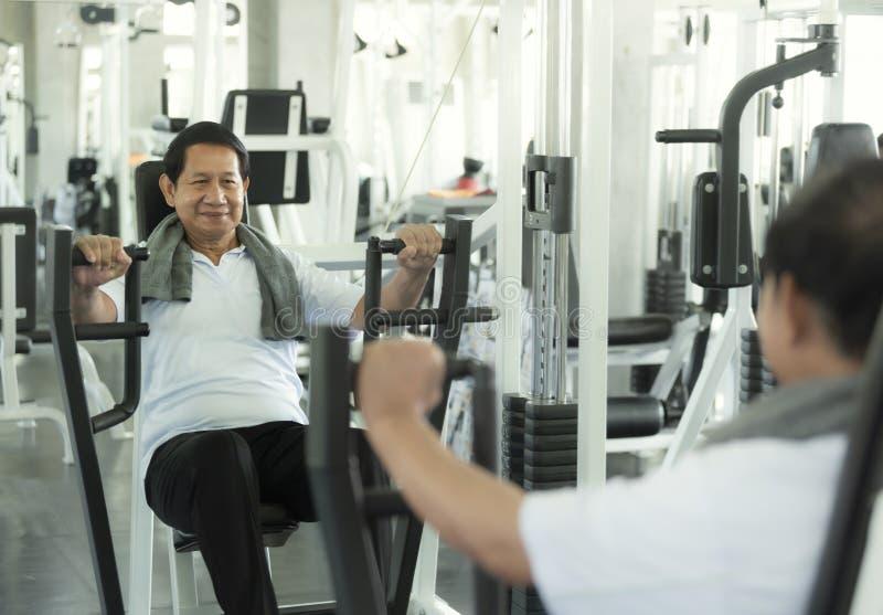 Pesa de gimnasia de elevaci?n del ejercicio asi?tico del hombre mayor en gimnasio de la aptitud forma de vida sana mayor imagenes de archivo
