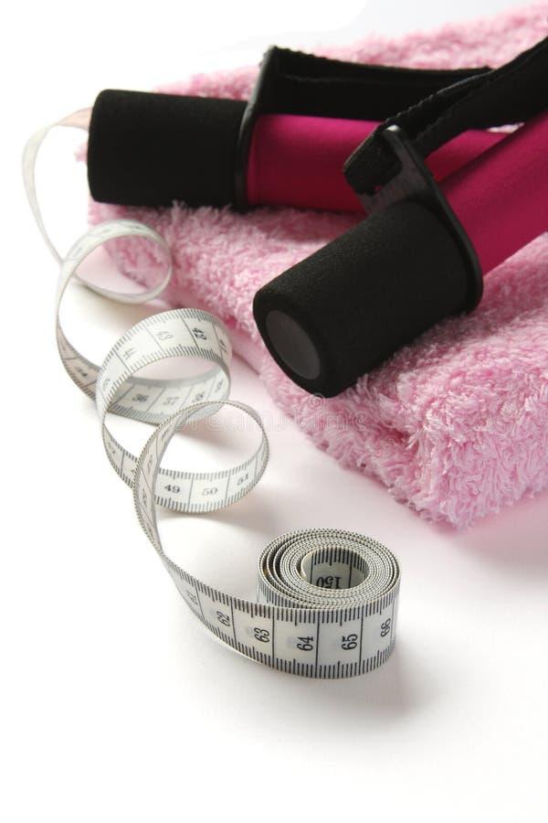 pesa de gimnasia Negro-rosada con la maneta y la cinta métrica en la toalla imagen de archivo