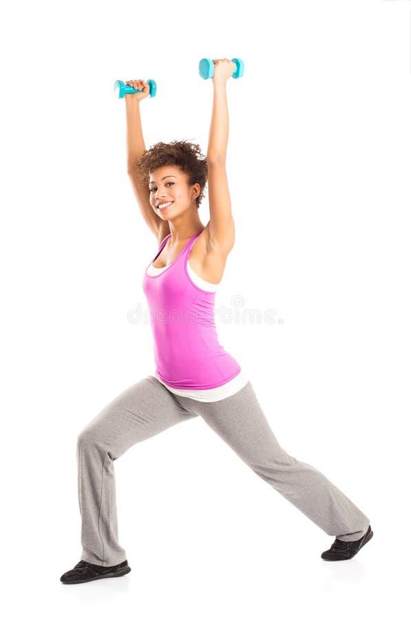 Mujer que ejercita con pesas de gimnasia fotos de archivo