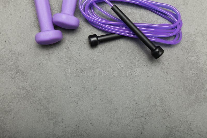 Pesa de gimnasia y cuerda en un fondo concreto Copie el espacio para el texto foto de archivo libre de regalías