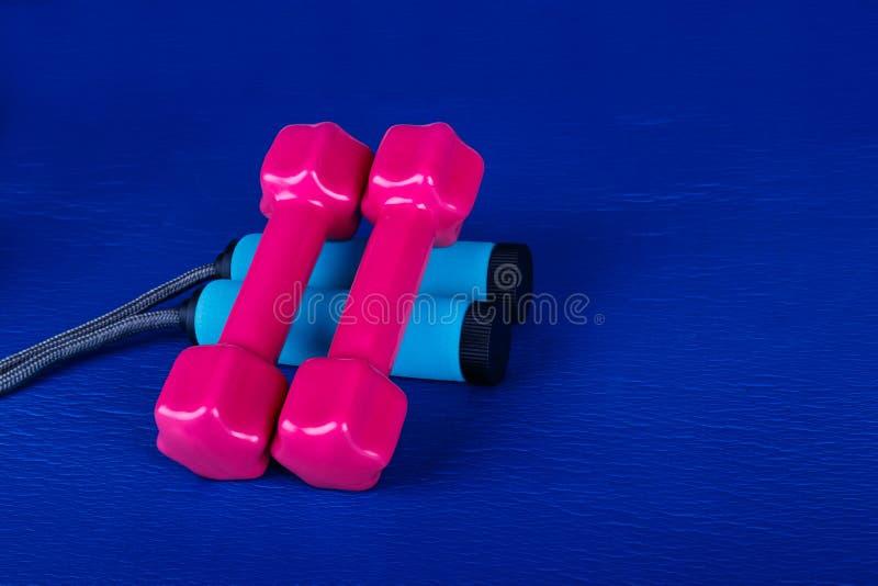 Pesa de gimnasia y cuerda que salta en la estera azul de la yoga fotografía de archivo