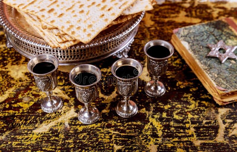 Pesach påskhögtidsymboler av stor judisk ferie Traditionellt matzoh, matzah eller matzo och vin i tappningsilverexponeringsglas royaltyfria foton