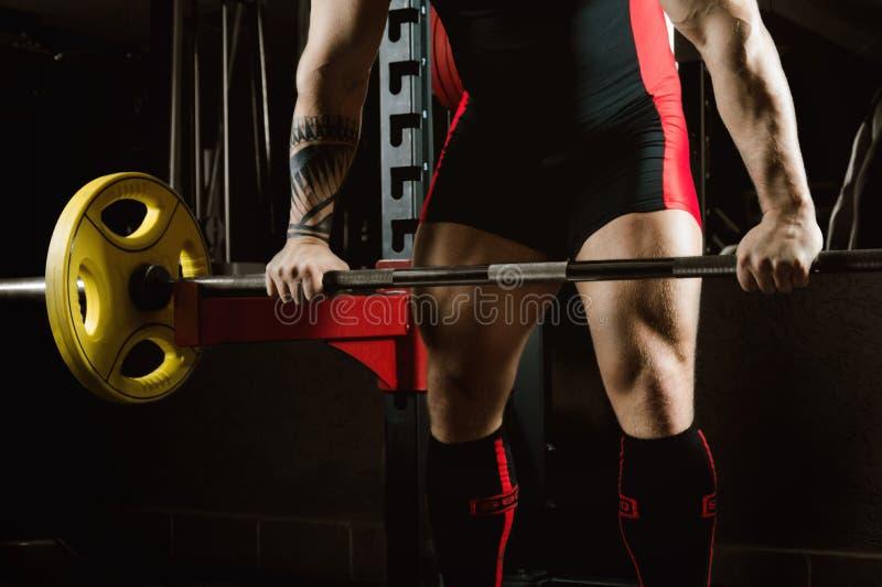 Pesadamente o atleta enorme aproxima a barra a fim executar um e fotos de stock royalty free