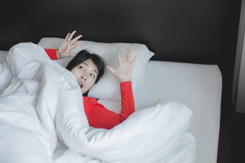 Pesadilla o mún sueño, mujer con susto y pánico mientras que se acuesta debajo de la manta en dormitorio foto de archivo