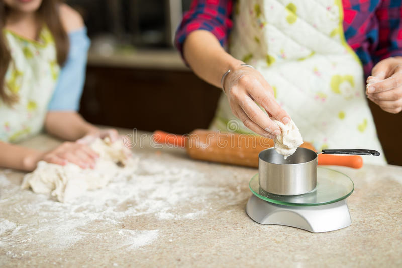 Pesage de la pâte sur une échelle photos stock